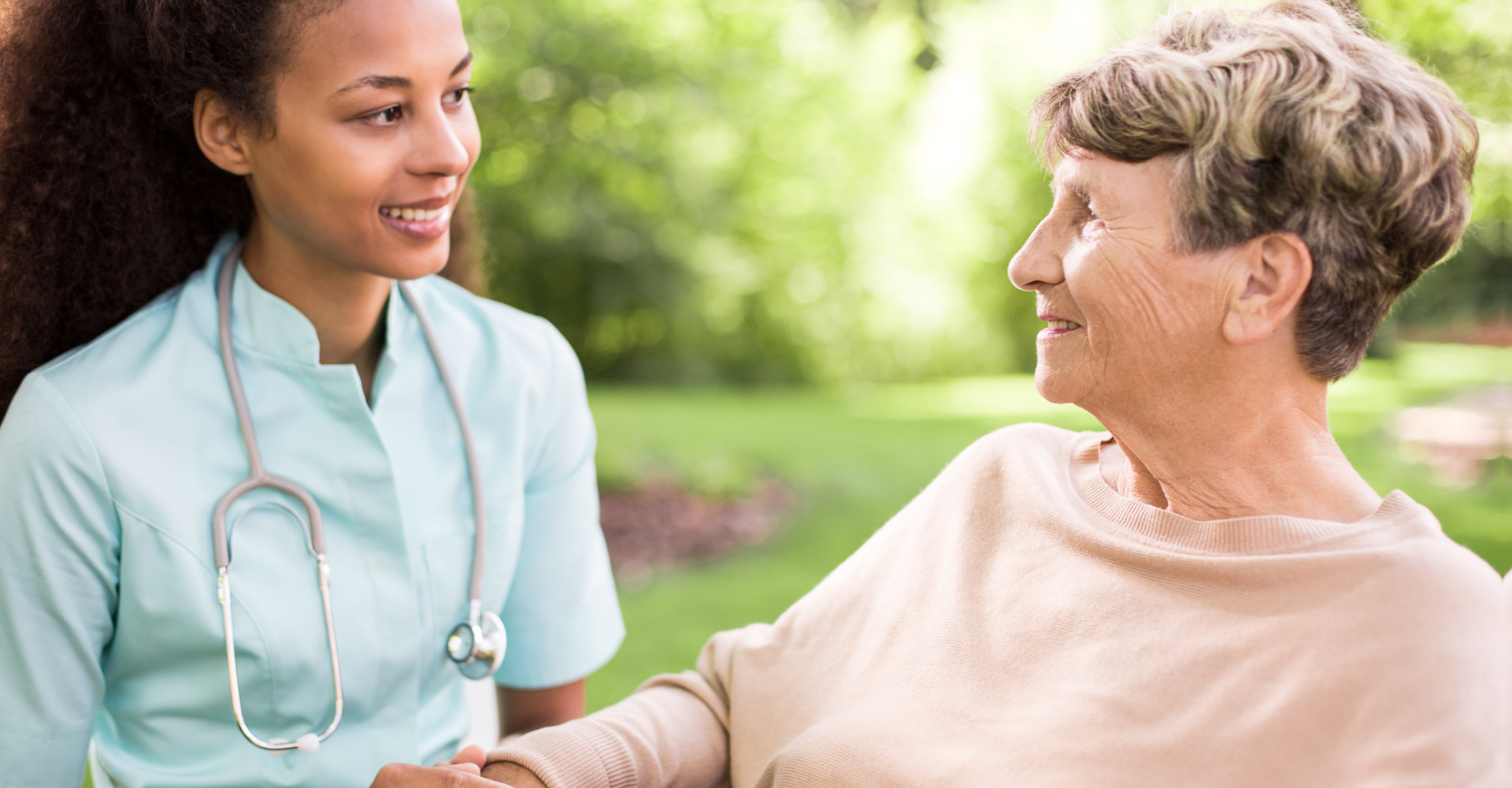 Caregiver and Senior Women facing each other while smiling