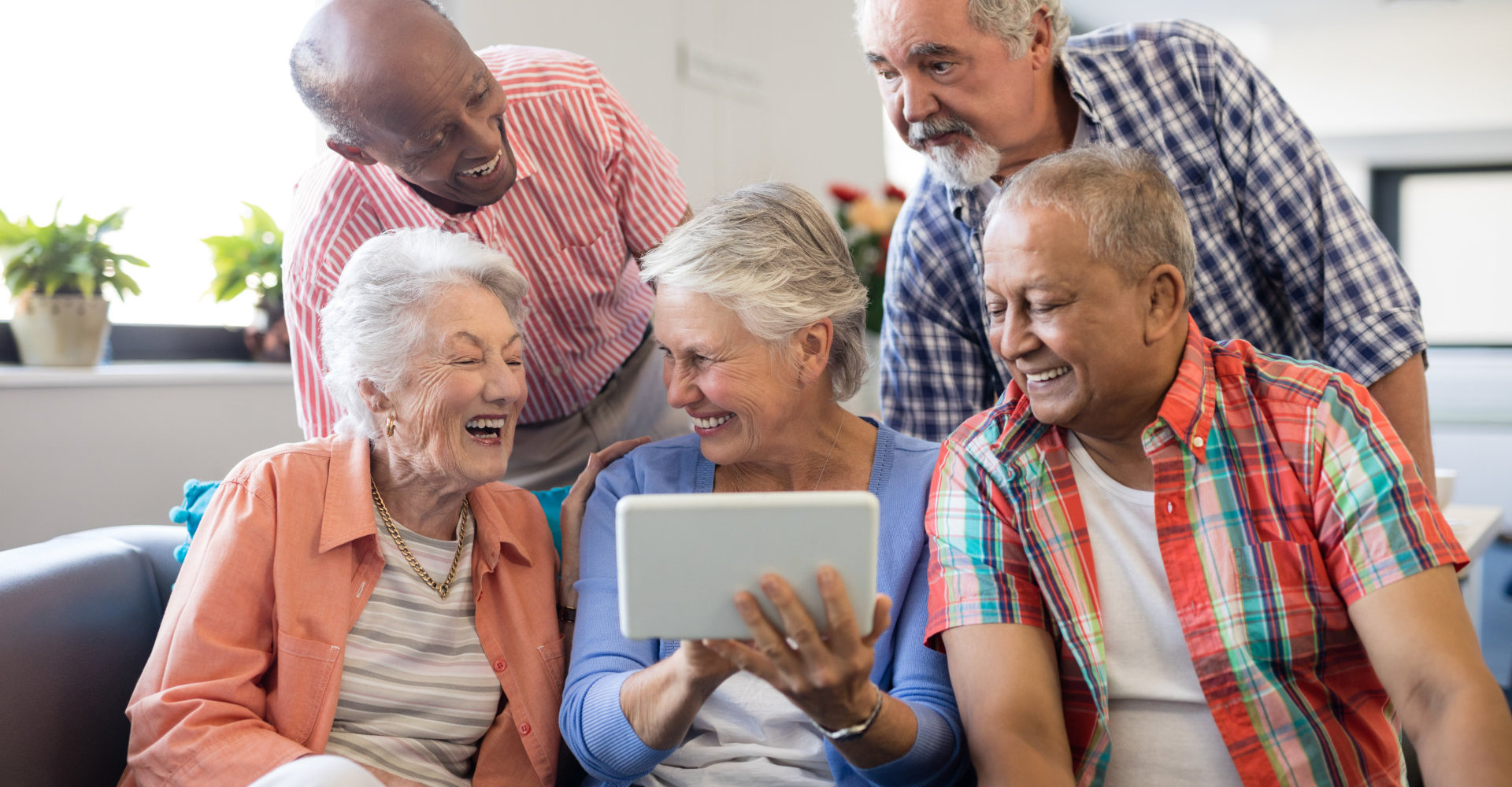 Senior woman showing digital tablet to cheerful friends