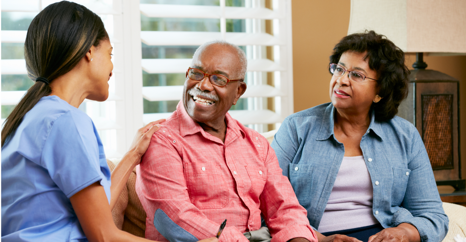elder couple and a caregiver talking