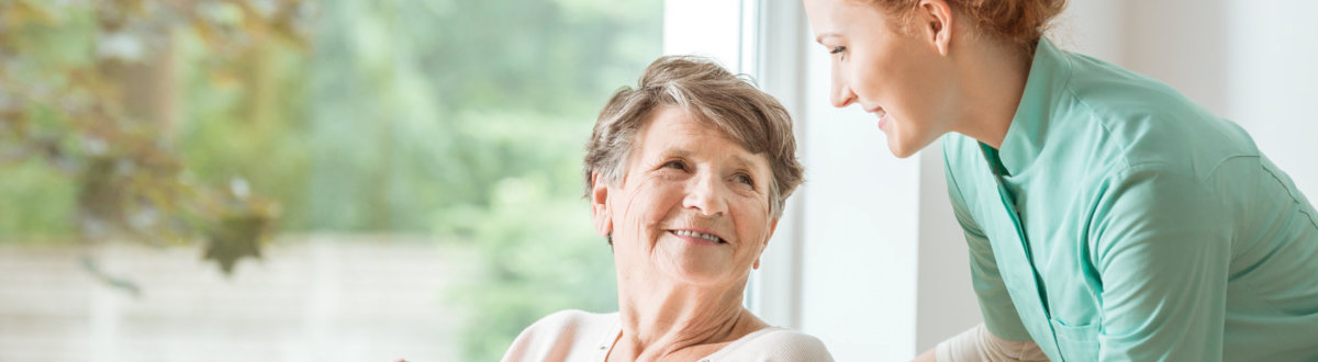 senior woman smiling with caregiver