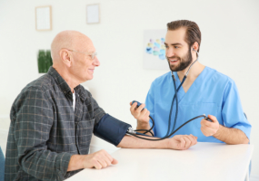 Young caregiver measuring blood pressure of senior man at home