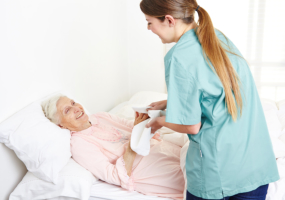 nurse washing bedridden senior woman and drying her hands in nursing hom